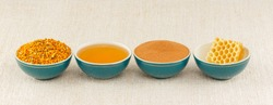 Honey, honeycomb, pollen granules and cinnamon in green porcelain bowls in a row, on rustic table cloth