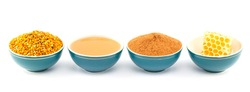Honey, honeycomb, pollen granules and cinnamon in green porcelain bowls in a row, on white isolated background