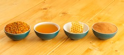 Honey, honeycomb, pollen granules and cinnamon in green porcelain bowls in a row, on wooden tabletop surface