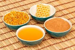 Honey, honeycomb, pollen granules and cinnamon in green porcelain bowls, on light rustic mat