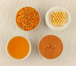 Honey, honeycomb, pollen granules and cinnamon in porcelain bowls, seen from above, on rustic table cloth
