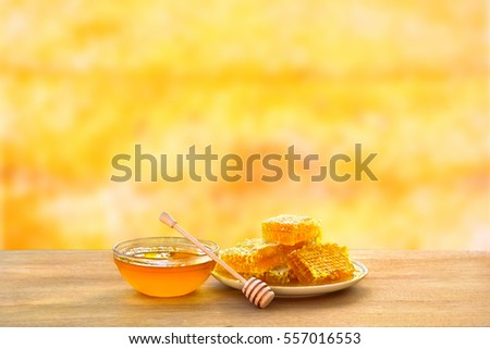 Honey in glass bowl, wooden honey dipper and honeycombs with honey on wooden table on background honeycombs with full cells of honey
