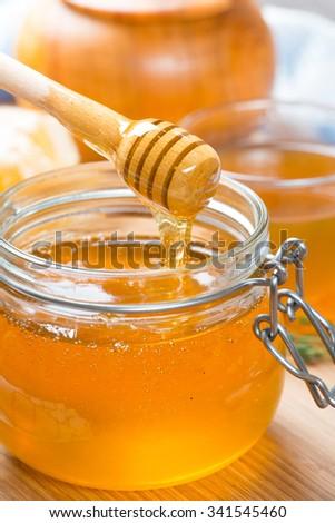 Honey in glass jar and honeycombs wax - Shutterstock ID 341545460
