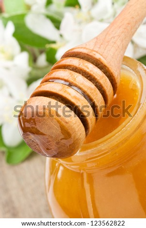 honey in glass jar and wooden stick on wood