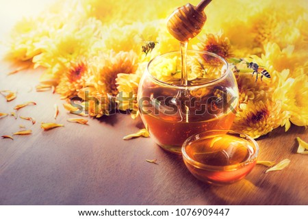 Photo of  Honey in glass jar with bee flying and flowers on a wooden floor.