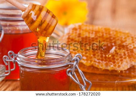 Honey in jar with honeycomb and wooden drizzler