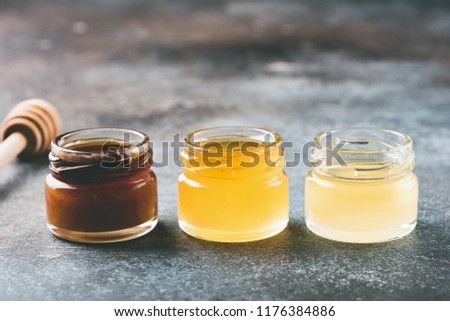 Honey in small jars and wooden honey dipper. Different types of honey. Closeup view, toned image, copy space for text