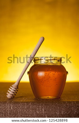 Honey jar with dipper on table, canvas background
