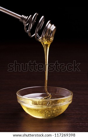honey jar with steel spoon and flowing honey