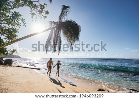 Honey moon on the sea shore. Back view of loving couple walking together on beautiful tropical white sand beach. Foto stock ©