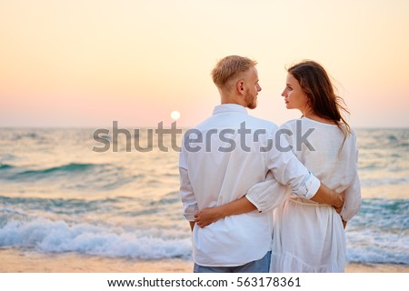 Honey moon on the sea shore. Romantic loving couple standing together on the beach enjoying sunset.