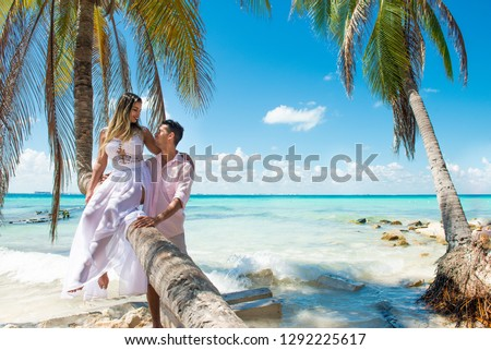 Honey mooners or newlyweds sitting at the palm tree in Cancun. They are looking each other.  Turquoise water is behind them. Honey moon concept. Romantic concept.  Holidays in a tropical country.