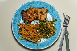 Honey mustard grilled chicken thigh dinner served with home-made shoestring French fries and vegetables
