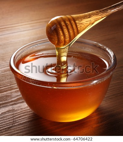 Honey pouring from drizzler into the bowl. Bowl is on a wooden table. - stock photo