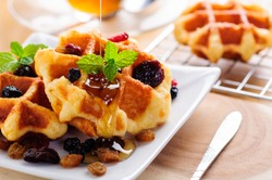 Honey pouring on a fresh waffles with dried fruits