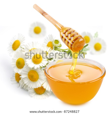 Honey pours with sticks in a jar. Flowers are near. Isolated on white background.
