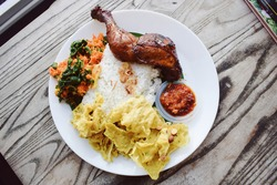 Honey roasted chicken rice with peanut chips, vegetables and chili spicy sauce. Indonesian tradisional dish.