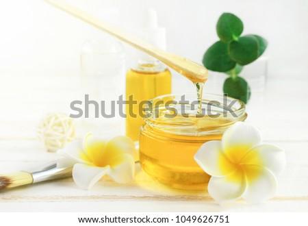 Honey spa treatment. Pouring sweet golden honey to jar, plumeria flowers, soft sunny light. Natural homemade skincare