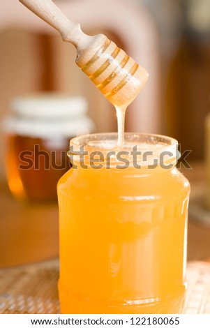 Honey stick in jar on the table