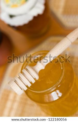 Honey stick on jar on the table
