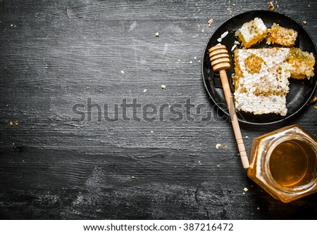 Honey style. A jar of natural honey and honey comb in the pan. On black rustic background.