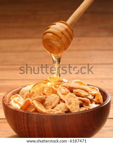 Honey with stick pouring into a cereal bowl