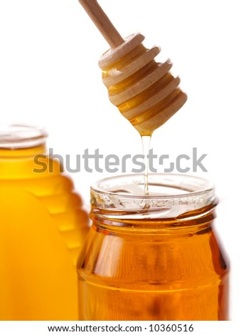 Honey with wood stick pouring