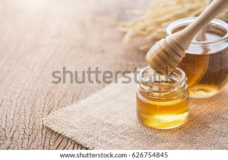 Photo of  Honey with wooden honey dipper on wooden table