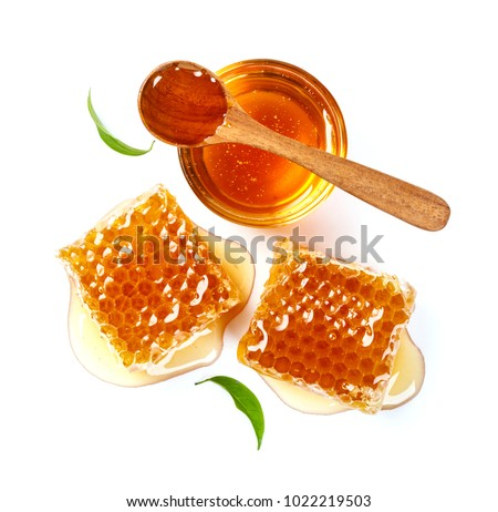 Honeycomb and honey in glass bowl and spoon, flower isolated on white background