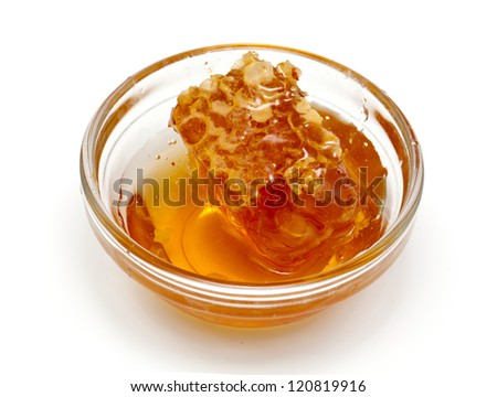 honeycomb in a glass bowl over white