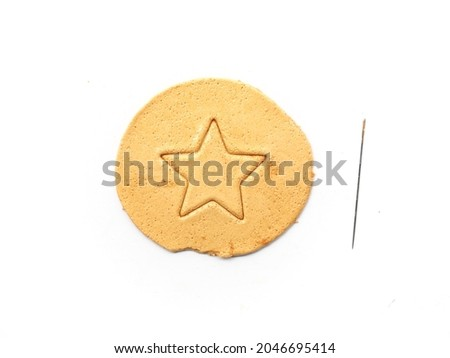 Honeycomb toffee sugar candy with star shape and needle to play Korean Dalgona or Ppopgi candy challenge game on white background