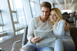 Honeymoon about to begin. Happy young beautiful couple embracing while waiting for their flight at the airport departure lounge reading a newspaper together honeymoon love youth adventures vacation