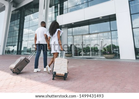 Honeymoon concept. Happy african newlyweds entering airport building with luggage, empty space #1499431493