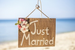 Honeymoon concept. Just married. Wooden plate on the tropical beach.