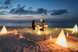 Honeymoon couple is having a private, romantic dinner at a tropical beach
