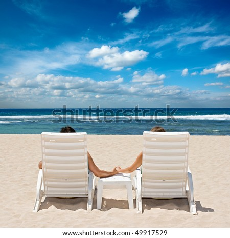 Honeymoon couple sunbathing in beach chairs