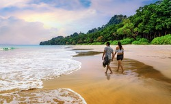 Honeymoon couple take a walk at the scenic Havelock islands beach at Andaman India.