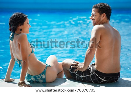 Honeymoon: happy young newlyweds smiling and relaxing near hotel pool. Horizontal shape, rear view, copy space