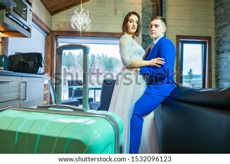 Honeymoon. Honeymooners looking at the suitcase. Groom hugs the bride. Newlyweds remembered about things. Travel after the wedding. Guy and a girl came to a country house. Concept-travel for lovers #1532096123