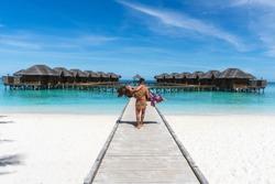 Honeymoon on Maldives. Man holding his wife on arms on bridge on ocean beach