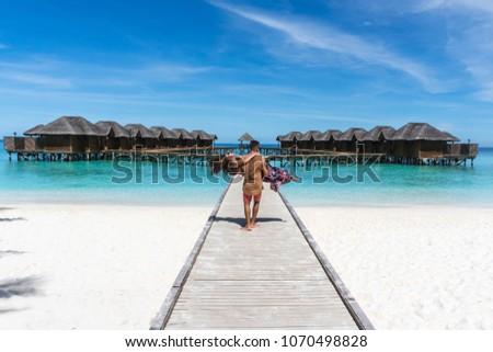 Honeymoon on Maldives. Man holding his wife on arms on bridge on ocean beach #1070498828