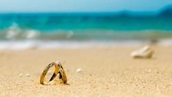 Honeymoon on tropical island, two wedding rings on the beach, sand, sky and ocean in the background
