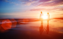 Honeymoon romantic couple in love walking on the beach on orange sunset background, happy young couple embracing enjoying ocean sunset during travel holidays vacation