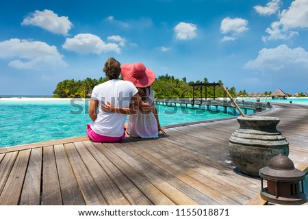 Honeymoon traveller couple hugging on a wooden jetty and enjoys their tropical holiday in the Maldives islands Foto stock ©