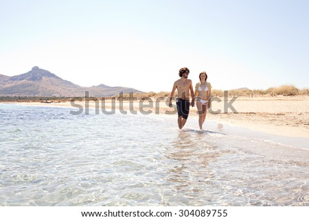 Honeymoon young couple holding hands relaxing and walking on the shore of a sandy beach with rolling mountains and blue sea water and sky, outdoors. Travel and tourism lifestyle, coastal destination.