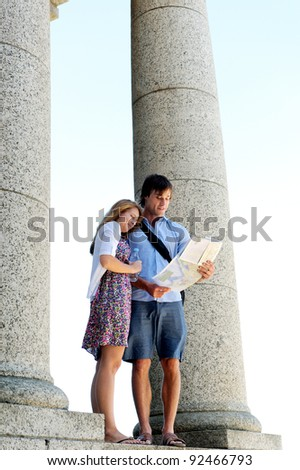Honeymooning tourists look a map while visiting an ancient monument