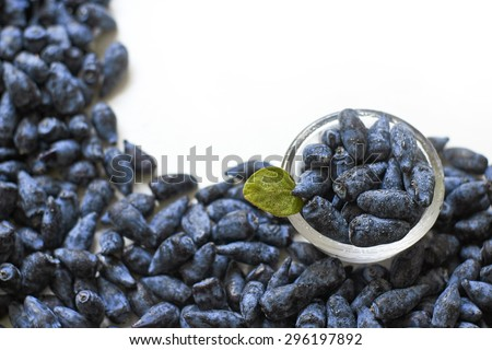 Honeysuckle blue berry fruits in a glass bowl on white background top view