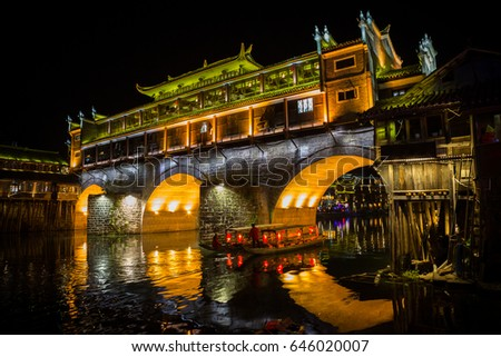 Hong Bridge or Rainbow bridge with tourist boat at night in Fenghuang Ancient town, Hunan province, China.one of the UNESCO World Heritage Tentative List in the Cultural category. #646020007