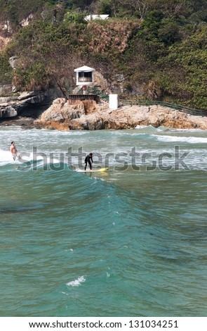 """HONG KONG - APRIL 10: Tai Long Wan beach """"Big Wave Bay"""" in Hong Kong on April 10 2011. Considered one of the most beautiful places in Hong Kong, it is a popular surf destination. - stock photo"""
