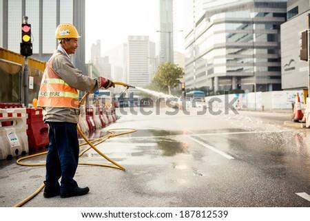 HONG KONG, CHINA - DECEMBER 22, 2013: Man cleaning road on December 22, 2013 in Hong Kong, China.